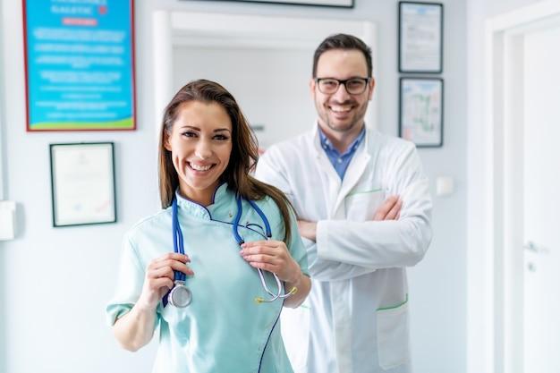 陽気な医師とクリニックの廊下でポーズの制服を着た看護師。腕を組んで医師。看護師の選択的な焦点。