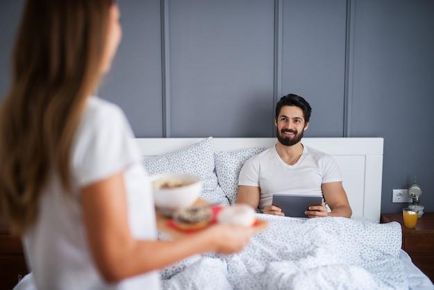 彼が自宅やホテルでタブレットからニュースを読んでいる間、彼のガールフレンドまたは妻を見て幸せな満足しているひげを生やした男はベッドで朝食をもたらします。