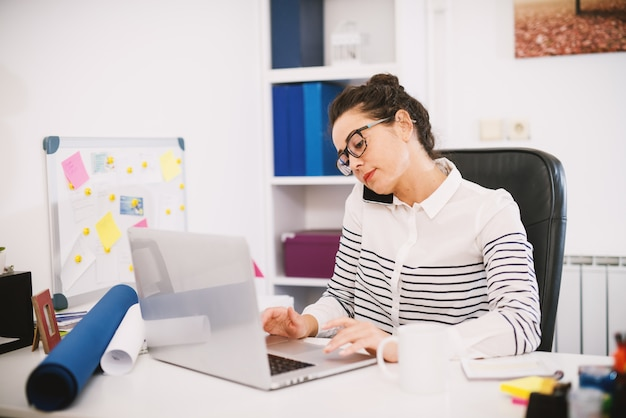 電話で話しているラップトップの前のオフィスに座っているスタイリッシュな美しいプロ忙しい女性の側面図を閉じます。