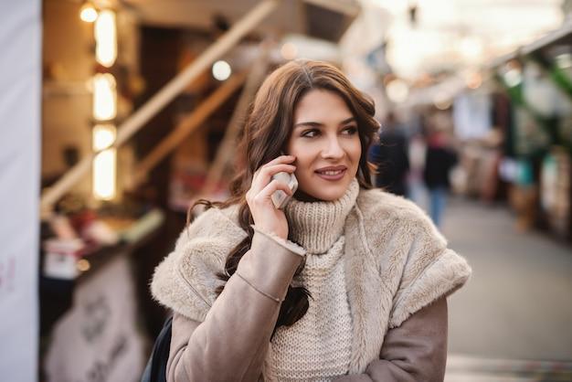 Молодая красивая женщина с длинными каштановыми волосами, стоя на улице в холодную погоду и с помощью смартфона.