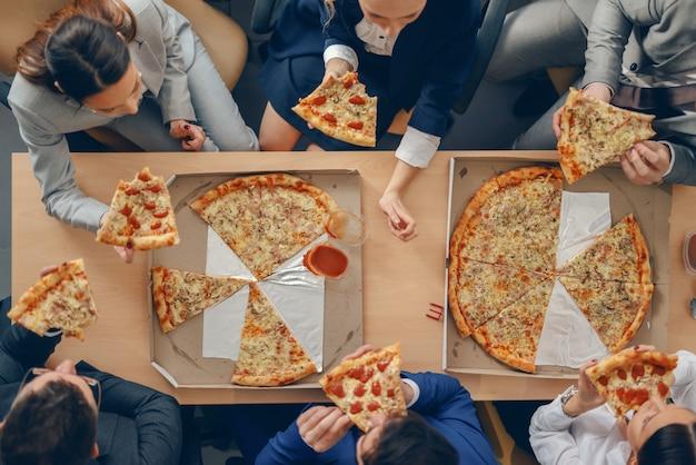 テーブルに座って、ランチにピザを持っているフォーマルな服装のビジネス人々の平面図です。