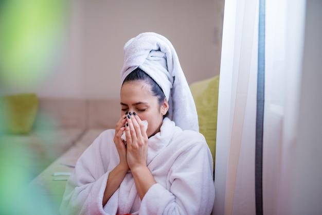 Молодая обаятельная красивая женщина в халате и с полотенцем на голове вытирает нос после чихания, сидя на полу, прислонившись к дивану.