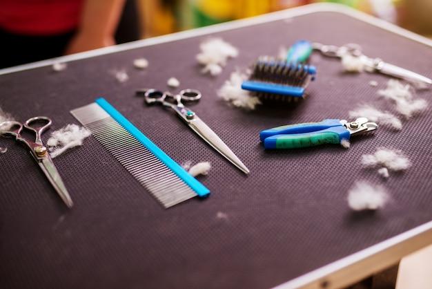 Инструменты парикмахера животных на столе, окруженном вырезанным мехом в животном салоне.