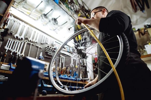自転車のホイールに空気をポンプする準備をしている若いプロの殺し屋。