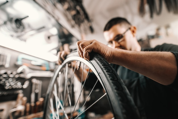 Человек преданный кавказцу кладя автошину на колесо велосипеда пока стоящ в мастерской.