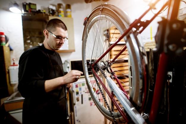 若い男がガレージで自転車のホイールバランスをチェックします。