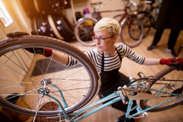 Привлекательная сфокусированная женщина проверяя баланс колеса велосипеда в солнечном гараже.