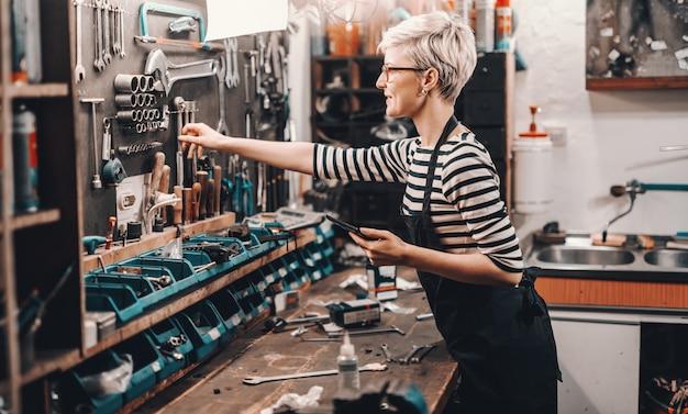 短いブロンドの髪と眼鏡を自転車を修理するツールの壁から取っている美しい白人女性労働者。自転車工房のインテリア。
