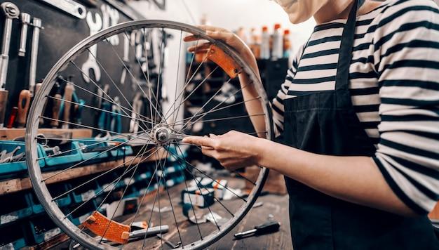 かわいい白人女性労働者が自転車のワークショップに立っている間自転車のホイールを押しながら修理します。