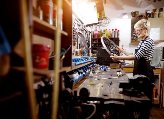 ワークショップで裸の自転車の車輪をチェック勤勉なプロの笑顔の女性。
