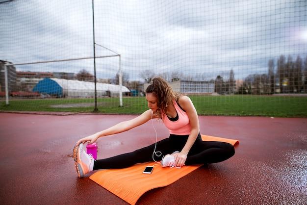 Привлекательная молодая спортивная женщина делает йога, протягивая бедра снаружи на оранжевой циновке.