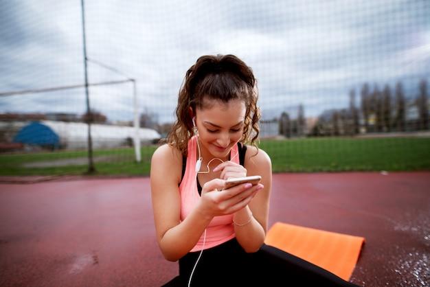 魅力的な若い陽気な女性がオレンジ色のマットの上に座っている間電話をチェックします。