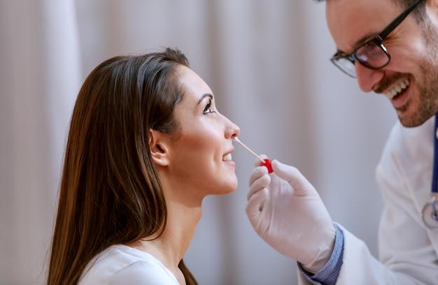 鼻からサンプルを取る医師のクローズアップ。笑顔の女性患者にセレクティブフォーカス。
