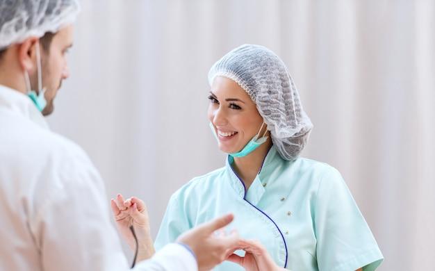 制服、医療用キャップ、手術成功後に医師に話しかける防護マスクの美しい笑顔の肖像画。