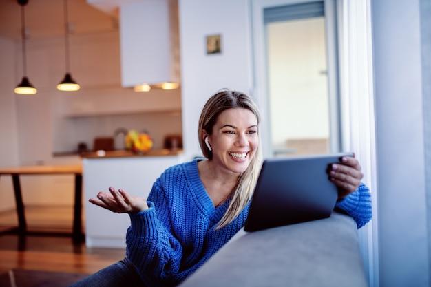 Шикарная усмехаясь кавказская молодая блондинка в голубом свитере и в джинсах сидя на софе и используя таблетку для видео-звонка. интерьер гостиной.
