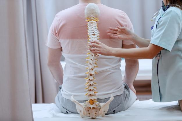Кавказская медсестра держит модель позвоночника на фоне спины пациента. интерьер клиники.