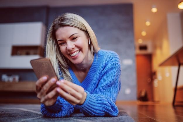 Очаровательная блондинка улыбается женщина в свитер, лежа на животе на полу в гостиной и с помощью смарт-телефона. в ухе есть блютуз наушники.