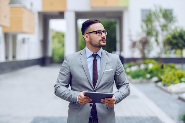 Привлекательный кавказский бизнесмен в костюме при серьезное выражение лица смотря отсутствующий и держа таблетку. бизнес центр экстерьера.