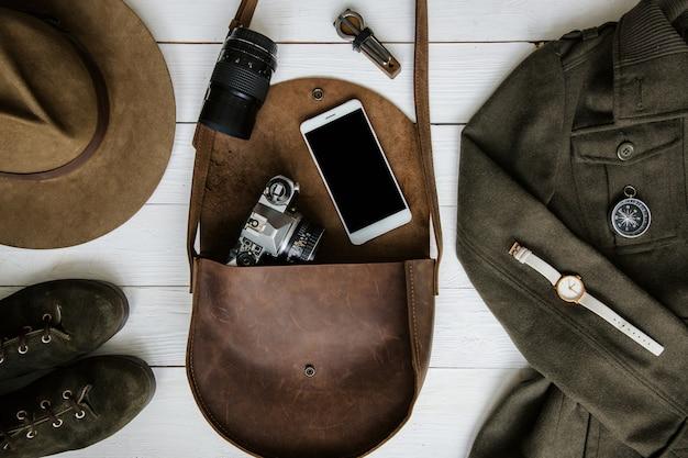 Женская одежда и аксессуары путешественника на белом деревянном фоне плоской планировки