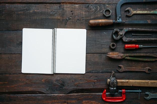 Набор старинных инструментов на темно-коричневом деревянном фоне и пустой блокнот