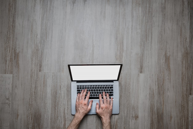 Человек руки печатать на клавиатуре ноутбука на пустой серый деревянный стол