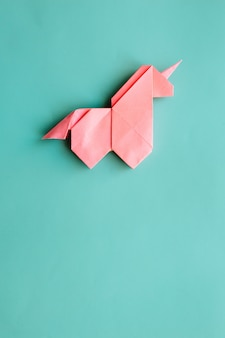 Розовый оригами единорог на голубом фоне