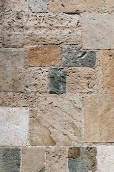 古代イタリアの砂岩教会の壁の垂直のクローズアップパターン