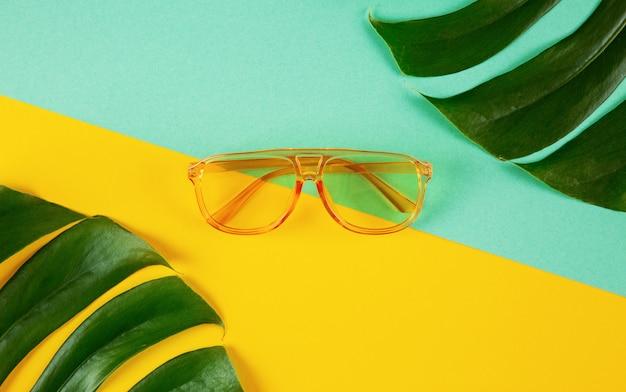 Модные полупрозрачные солнцезащитные очки на абстрактной цветной бумаге с тропическими листьями
