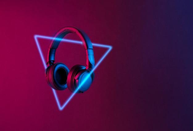 Черные беспроводные наушники и неоновый треугольник, освещенный красочным светом, плавающим на абстрактном фоне с копией пространства