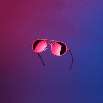 抽象的な暗い背景に浮かぶネオンの光で照らされたスタイリッシュなラウンドヴィンテージサングラス