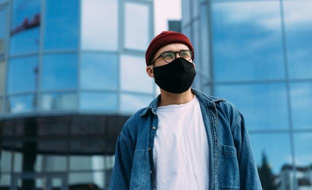 離れて見て黒いウイルスマスクを身に着けているビジネス地区のスタイリッシュな男性ヒップスター。コピースペース。ウイルスの概念。