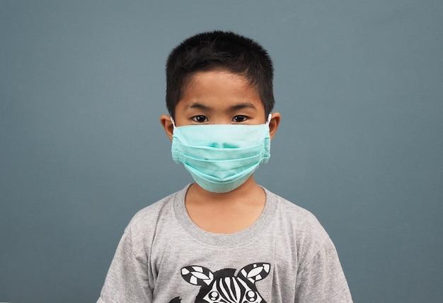 灰色の背景に防護マスクを着ている少年。