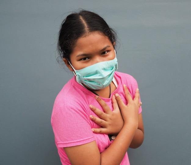 灰色の背景に胸に手を押しながら防護マスクを着ている少女。