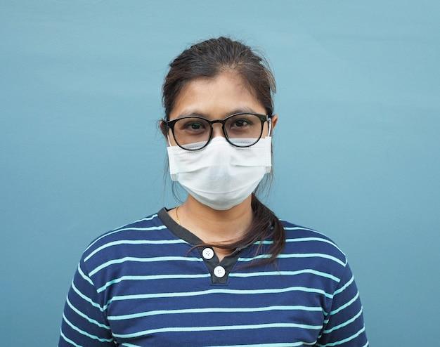 青色の背景にメガネと防護マスクを身に着けているアジアの女性の肖像画。