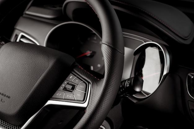 Руль нового автомобиля крупным планом, интерьер кабины, электрические кнопки