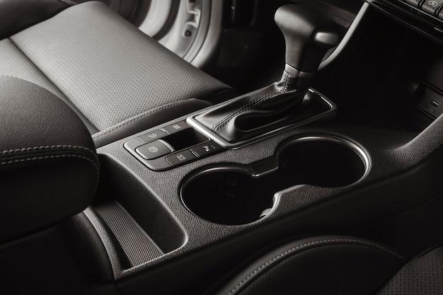 Салон автомобиля с черными кожаными сиденьями и автоматическим рычагом переключения передач