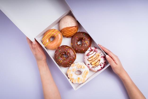 甘いドーナツ-カラフルな写真-トップビューのボックスを保持している若い女性