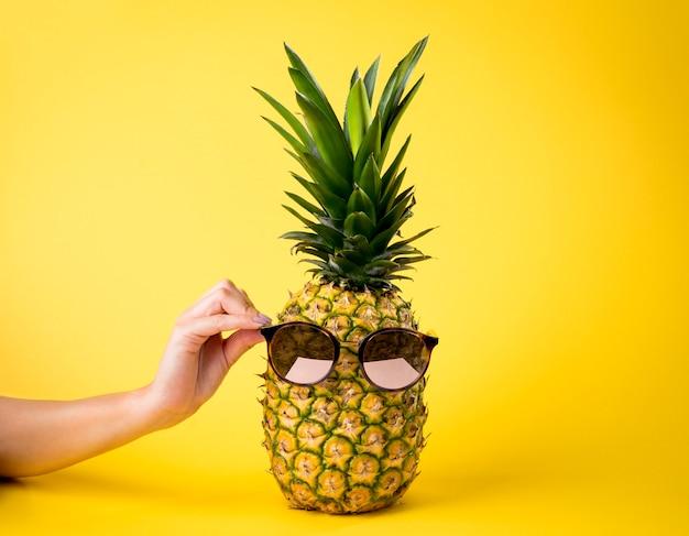 Сочный ананас с солнечными очками, концепция летних каникулов, женская рука, желтая предпосылка - питательный плодоовощ.