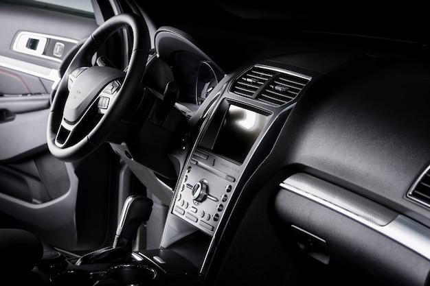 Вид на салон внедорожника, современная приборная панель с сенсорным экраном, черные кожаные сиденья, идеальные для водителя