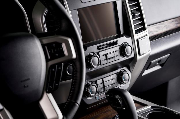 高級車のステアリングホイールとマルチメディアスクリーンを備えたダッシュボード、ドライバーにとって快適なインテリア