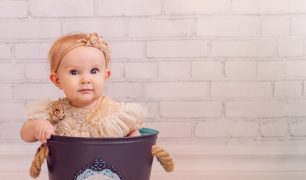 創造的な装飾のバケットバッグでかわいい新生児。ボウルの中に座っている幼児の女の子。ピンキーカラー