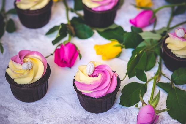 フクシアと黄色のバラの花とピンクと黄色のカップケーキ