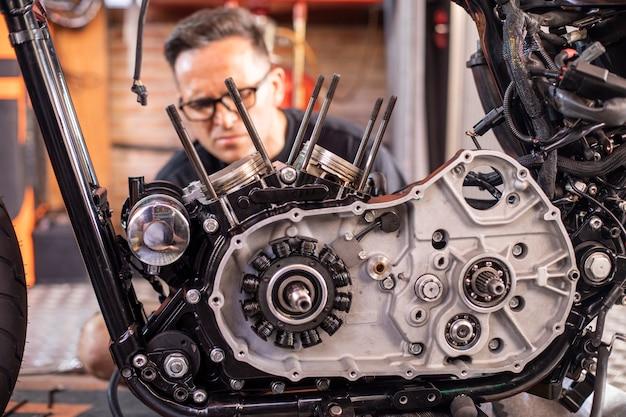 Механик работает по ремонту мотоцикла в мастерской