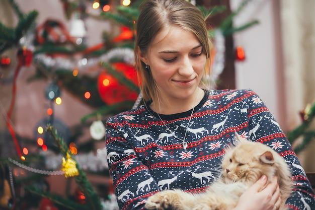 Девушка играет с кошкой на фоне елки