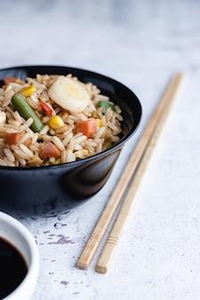 中華野菜チャーハンと卵を箸と醤油で器に盛り付けたもの。中華料理