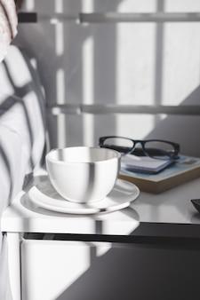 ナイトテーブルにお茶のカップ。ライフスタイル。