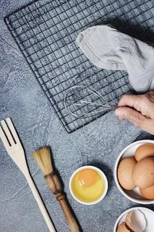 Ингредиенты и посуда для приготовления торта на синей поверхности. яйца, мука, корица, молоко. вид сверху. копировать пространство