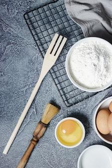 Ингредиенты и посуда для приготовления торта на текстурированной синей поверхности. яйца, мука, корица, молоко. вид сверху. копировать пространство