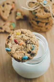 木の板にカラフルなチョコレート菓子と牛乳と自家製砂糖クッキーのガラス。スペースをコピーします。上面図。
