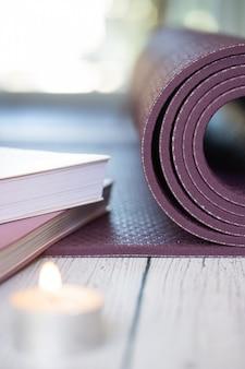 Конец-вверх фиолетовой циновки йоги с книгами и свечами на белом деревянном поле.